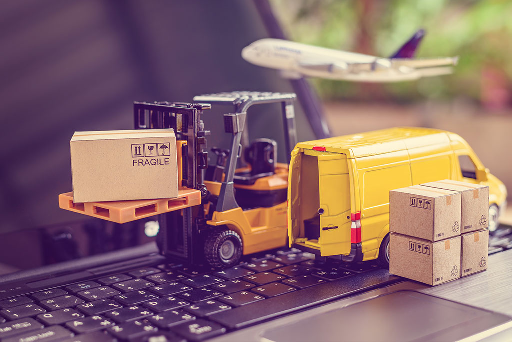 Miniature forklift, delivery van and airplane with parcels on a laptop