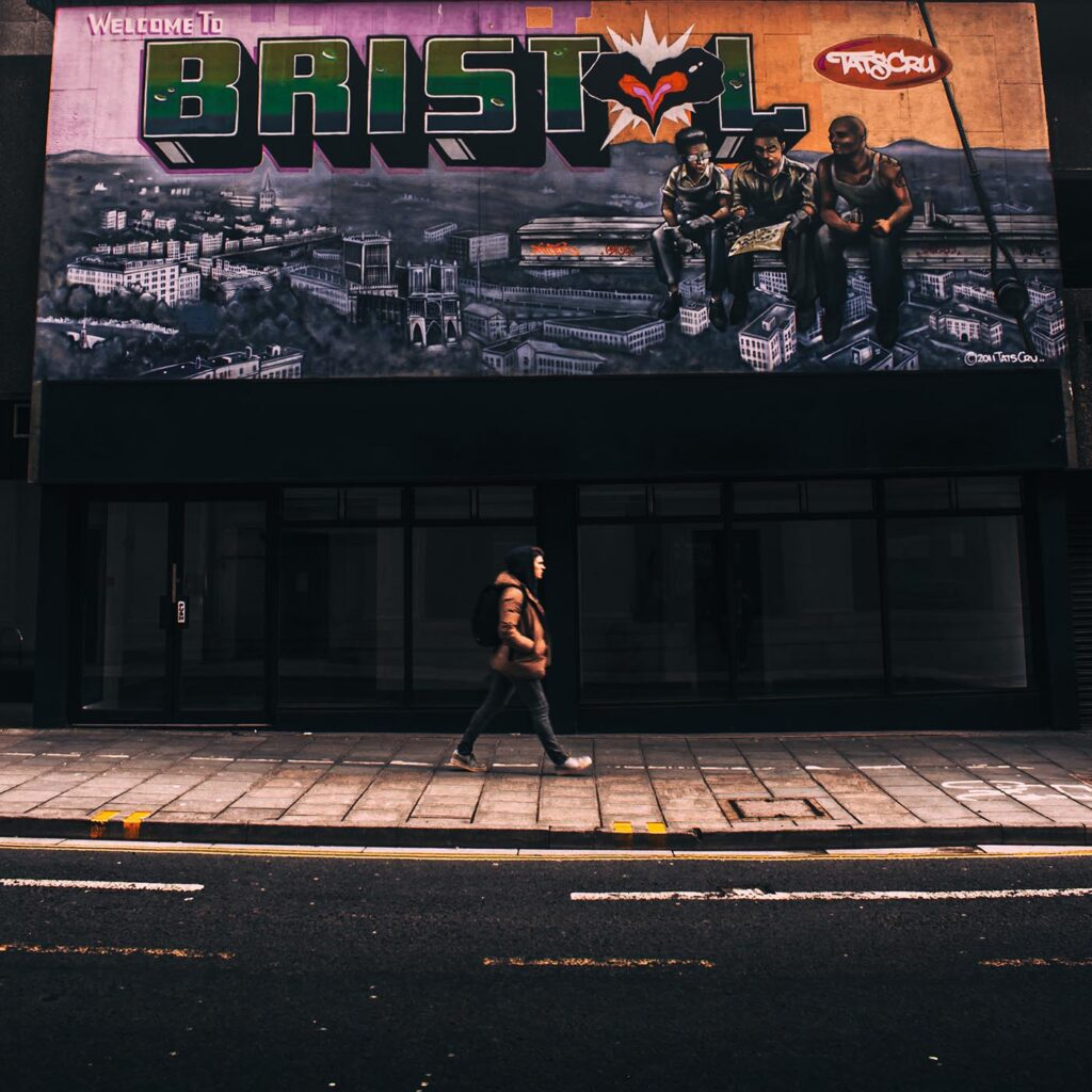 Member of public walking in front of a Bristol graffiti wall