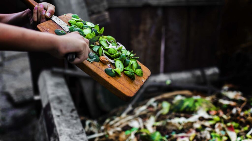 Putting old food into a compost heap