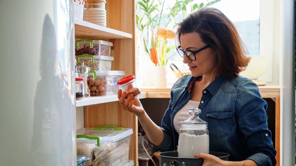 A lady looking at food in air tight containers