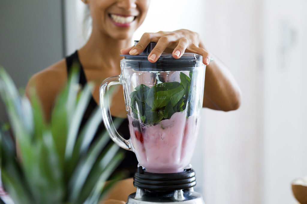 A lady making a homemade smoothie
