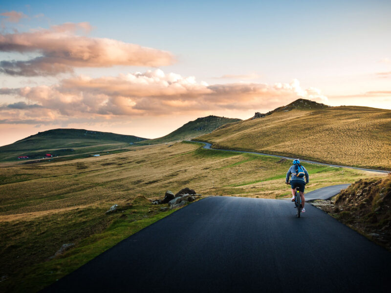 cyclist on empty road with mountains in front