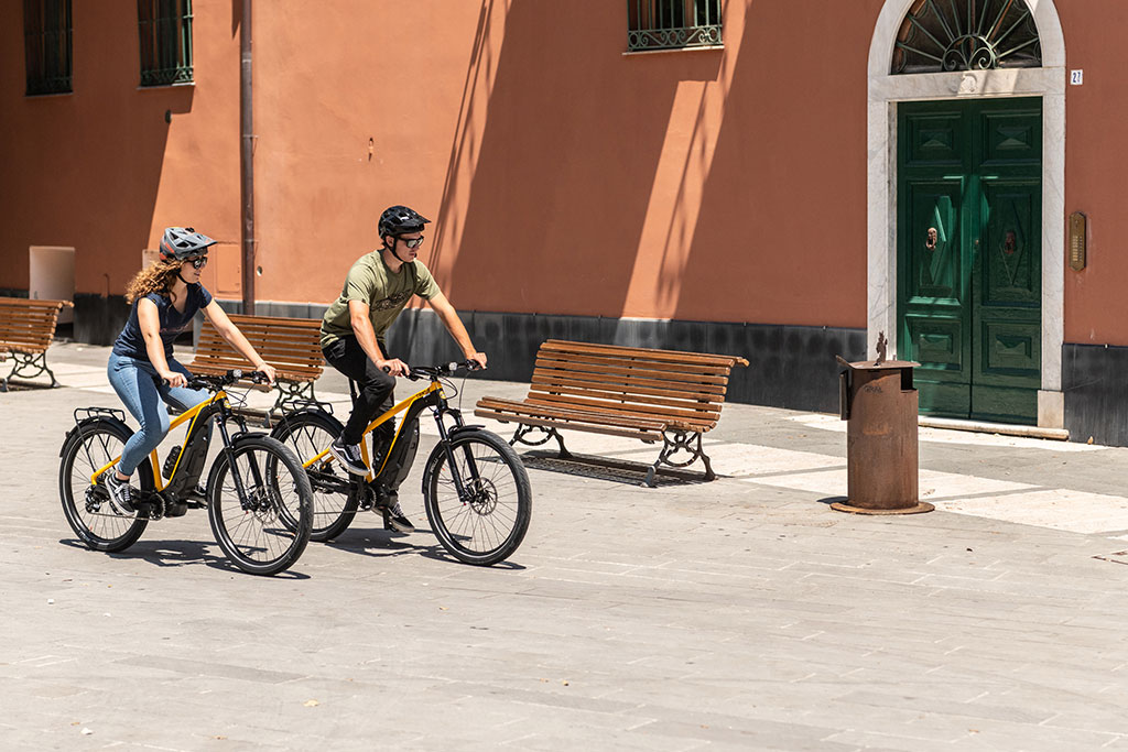 A couple cycle through a city on the Ducati e-scrambler