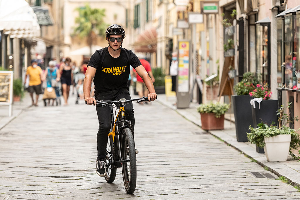 A man using the Ducati e-scrambler on cobbled streets in an urban environment