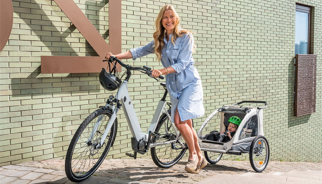 Mother using an e bike with child trailer attached