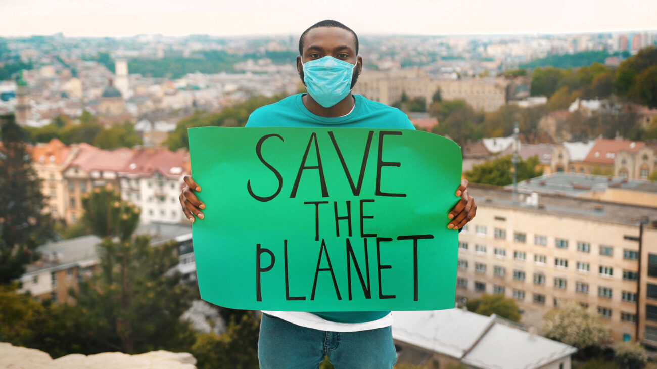 Man holding a sign saying Save The Planet