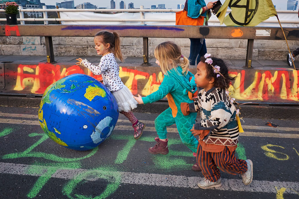 London / UK - April 2019: Three girls chasing an inflatable Earth globe during Extinction Rebellion protest