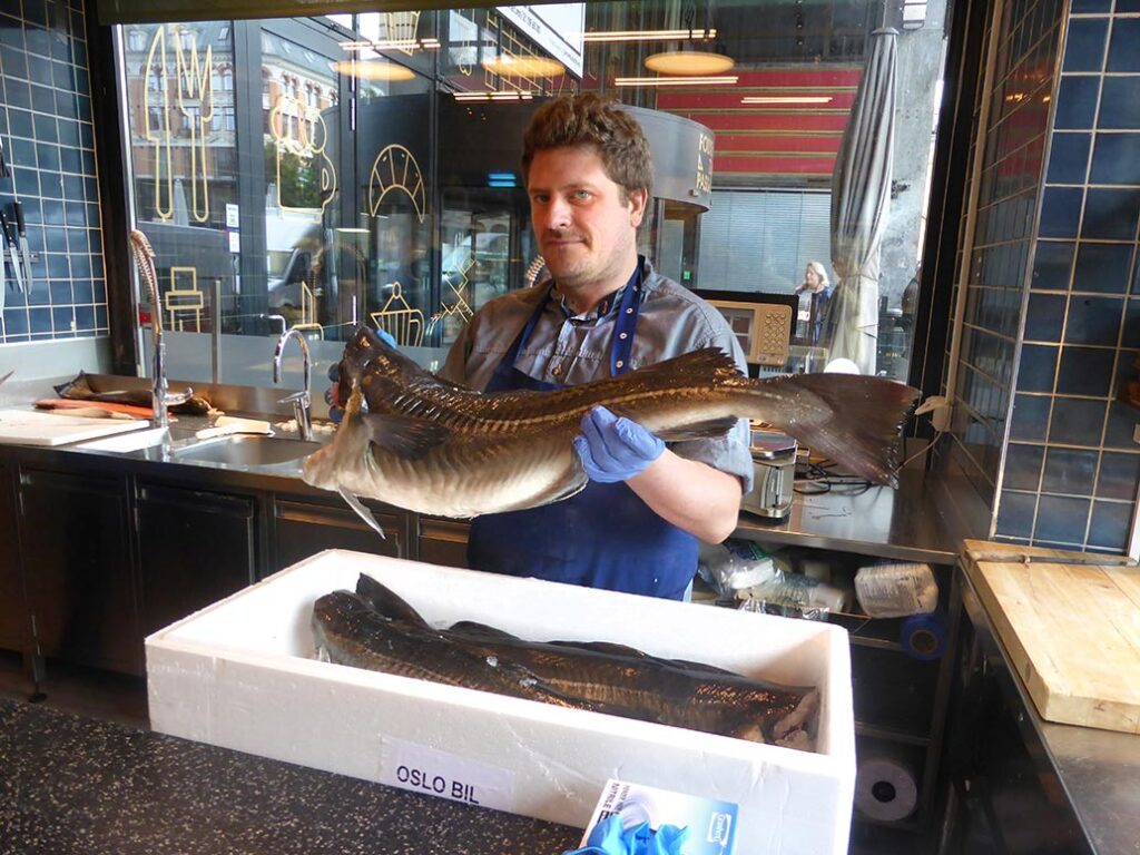 A fishmonger displays a cod in Oslo, Norway.