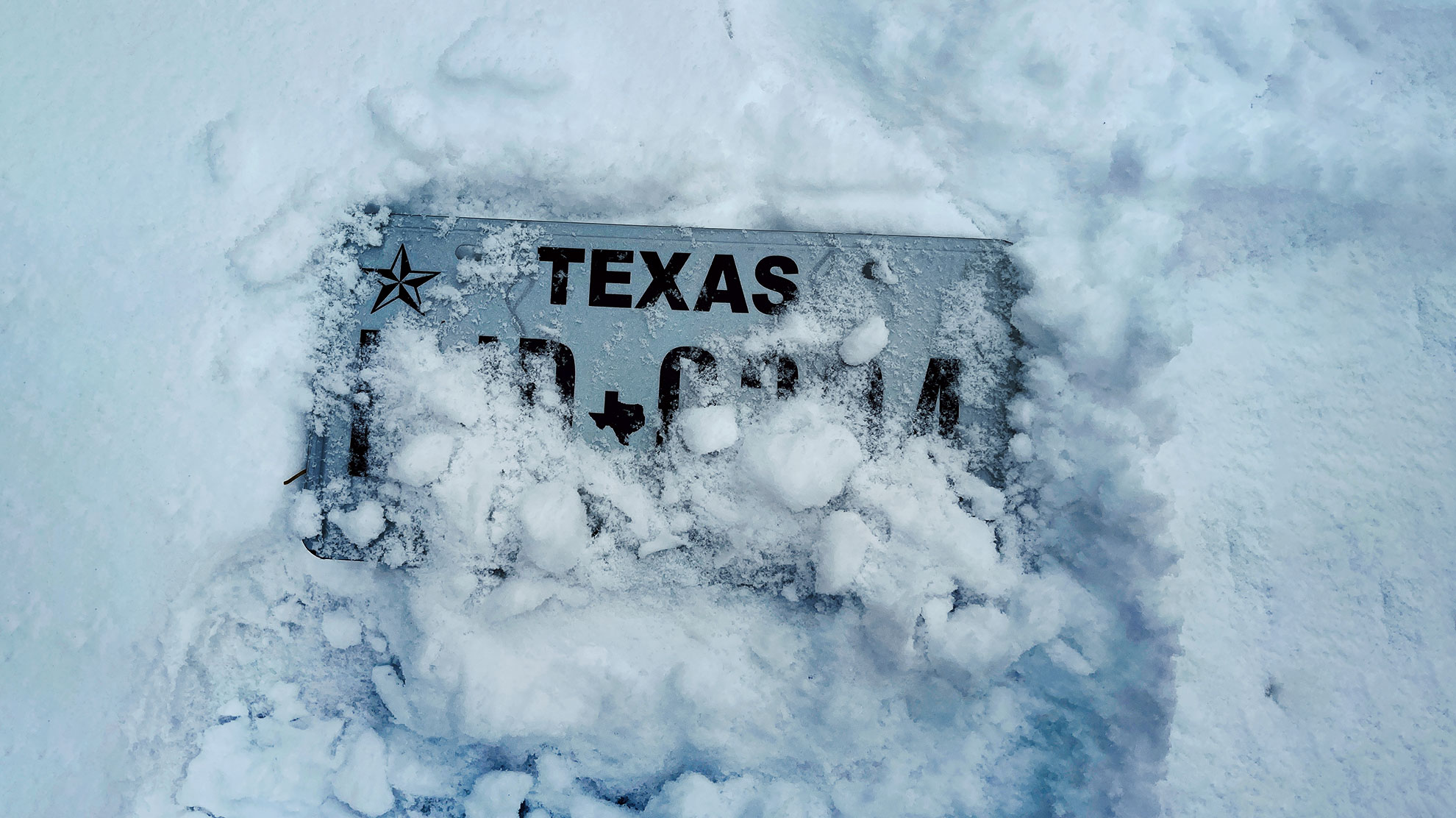 Texas license plate under snow