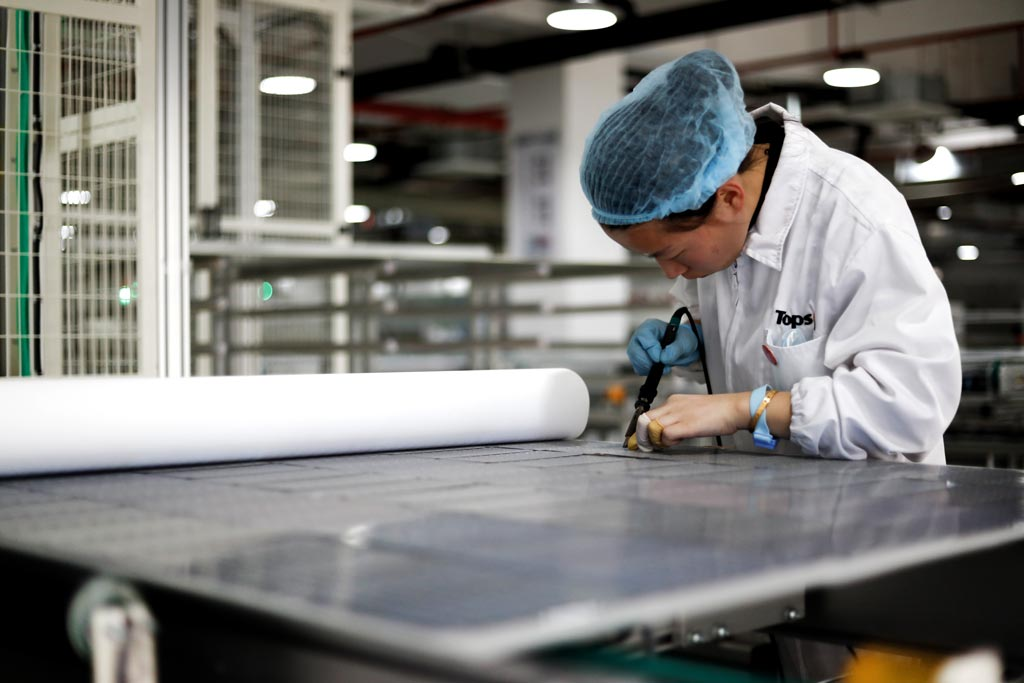 Workers operate equipment to produce photovoltaic circuit boards at a production workshop of a green energy technology company in Jiujiang, Jiangxi province.