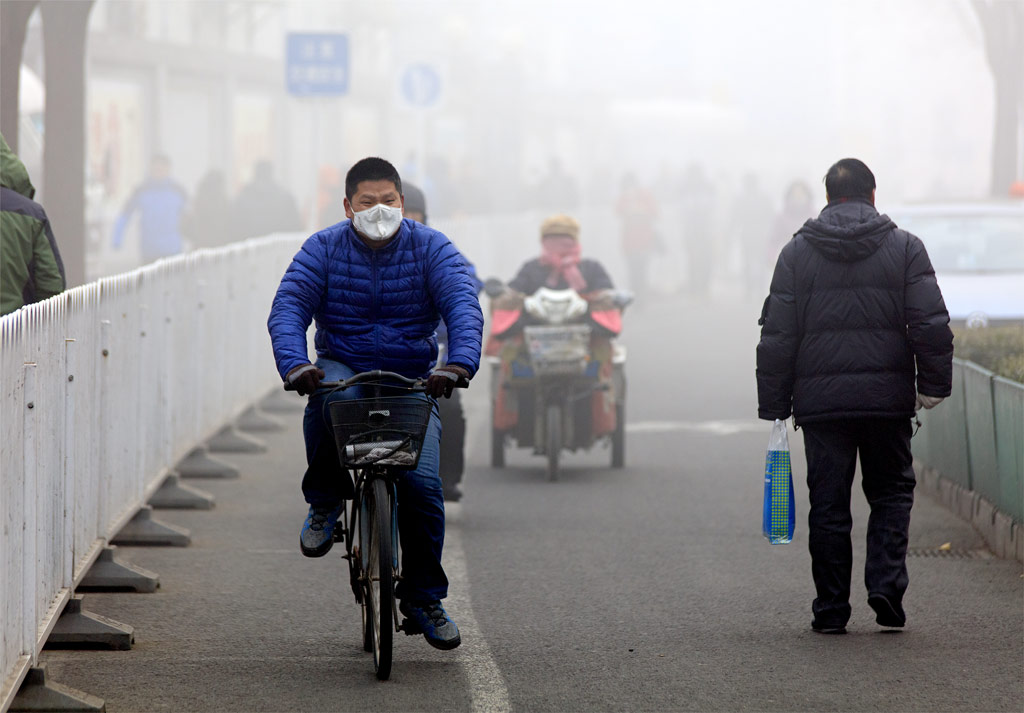 A man ride a bicycle in smog, after Beijing issued a red alert for air pollution