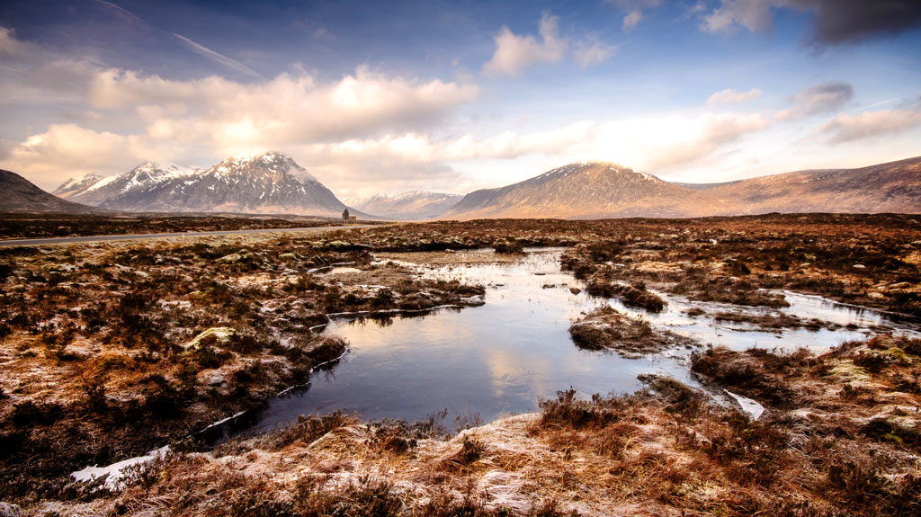 Vast wetland peat bog landscape of Rannoch Moor, with Buachaille Etive Mor and the mountains of Glen Coe rising in the distance