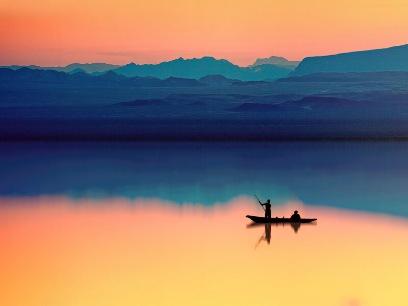 Sunset on a lake with a fishing boat