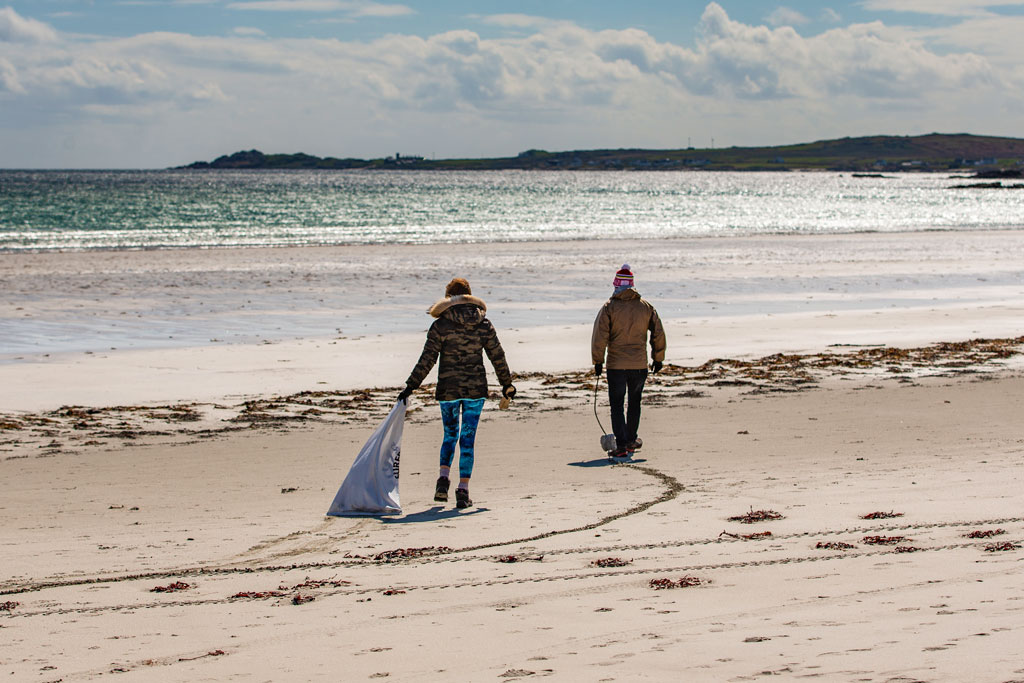 Two people on a beautiful beach doing a beach clean carrying a white rubbish bag -  Isle of Tiree, Argyll, UK